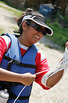 Young Asian Indian woman wears a life vest and winds rope in preparation for a river canoe trip.