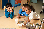 Preschool 3-4 year olds classroom job girl helping to put breakfast food on table wearing plastic gloves other students laughing and happy horizontal