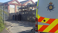 """Pictured: Police at the scene of the stand-off in Tredegar, Wales, UK.<br /> Re: The victim of a machete attack which led to an armed siege has been photographed showing his injuries.<br /> The man has been named locally as Nigel Davies, 57, who was assaulted with the weapon in the street two days ago.<br /> His attacker fled into a nearby derelict building where he spent 48 hours in a tense stand-off with armed police.<br /> But he was arrested early this morning(thurs) and is being questioned about a number of incidents.<br /> The graphic picture of Mr Davies was posted on social media after he was found covered in blood following the street attack in Tredegar, South Wales.<br /> He was treated in hospital for his facial wounds but is now at home with his family.<br /> An eye-witness at the scene of the siege said: """"The police are saying there is no danger to the public.<br /> """"But you can see from the picture that the victim was viciously assaulted with a weapon.""""<br /> Gwent Police confirmed that armed police were deployed after reports of a man armed with a machete was holed up inside the building on an industrial estate.<br /> Officers used riot shields to protect themselves when the man started throwing chunks of masonry at the them."""