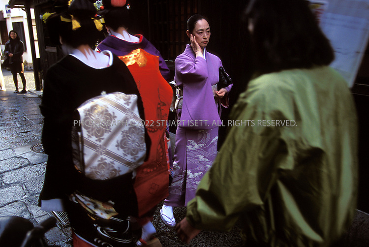 Kyoto, Japan..Mineko Iwasaki, once Kyoto's most famous geisha, wanders the back streets of the city's Gion District as 2 real geisha walk past...All photographs ©2003 Stuart Isett.All rights reserved.