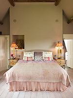 A pale pink bed throw and matching bedside tables and lamps contribute to the feminine atmosphere in this bedroom