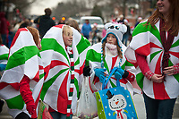 Children wearing Christmas ment costumes walk in the Christmas Parade route waiting for the arrival of Santa at the end.