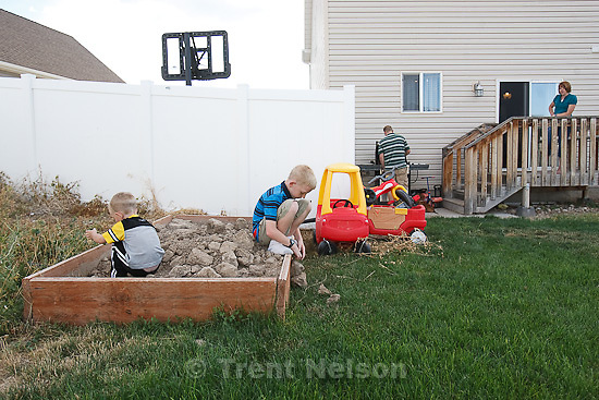Trent Nelson  |  The Salt Lake Tribune.Zachary and Spencer Burton, left, play in the backyard of their family's home with their parents Scott and Angela Burton in the background, Thursday, August 25, 2011. The Burton family are trying to sell their home in Tooele, Utah, due to a job transfer. Despite adding more than $20,000 in improvements since they purchased their home in 2005, they are now asking only what they paid for the home.