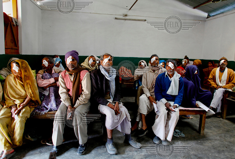 Patients await the removal of their bandages after their cataract operations at the GETA eye hospital. However, the hospital is too crowded to accommodate them so they all have to stay in the same room.