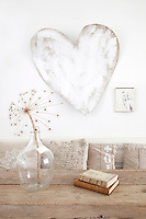 A cardboard heart is mounted on the wall above the kitchen table