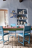 In the dining room Henri II chairs are painted a vibrant turquoise and set around an old gaming table