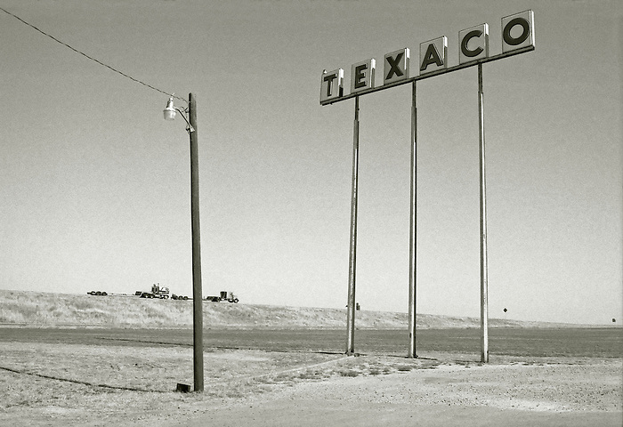 A huge TEXACO fuel sign looms over the Interstate in the American West. Two long haul rigs are dwarfed on the horizon. 1989.