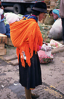 A woman carries her baby in a shawl on her back, Tambillo Market.