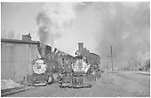 Head on view of two locomotives by engine house.<br /> D&amp;RGW  Montrose, CO