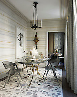 Jacques Adnet chairs surround a 1940s dining table by Roger Thibier; the chandelier is from the 1840s, and the rug is custom made; the drawing is by Konstantin Kakanias; the sconce is by Willy Daro, and the walls are sheathed in a custom-made wallpaper