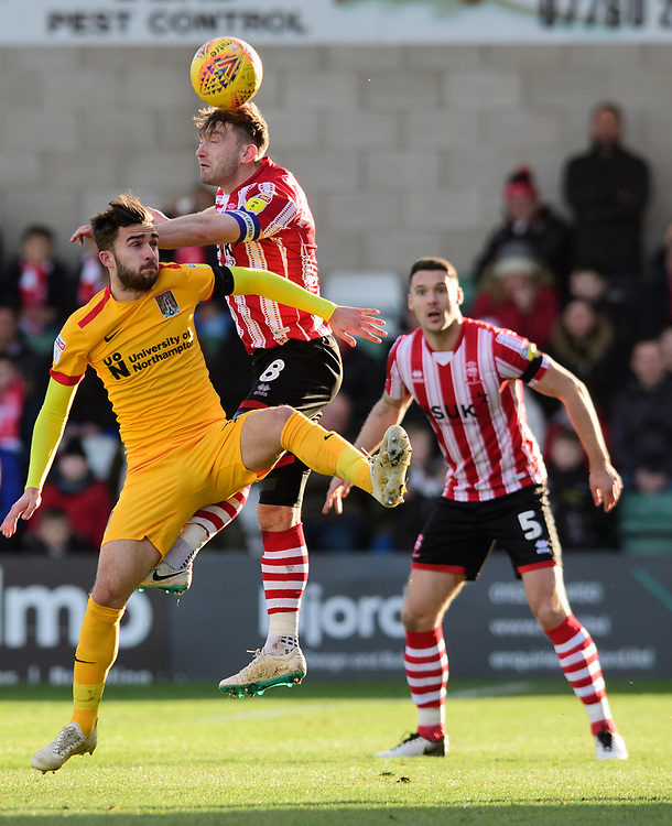 Lincoln City's Lee Frecklington vies for possession with Northampton Town's Jack Bridge<br /> <br /> Photographer Chris Vaughan/CameraSport<br /> <br /> The EFL Sky Bet League Two - Lincoln City v Northampton Town - Saturday 9th February 2019 - Sincil Bank - Lincoln<br /> <br /> World Copyright © 2019 CameraSport. All rights reserved. 43 Linden Ave. Countesthorpe. Leicester. England. LE8 5PG - Tel: +44 (0) 116 277 4147 - admin@camerasport.com - www.camerasport.com