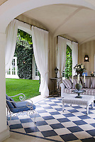 The loggia is furnished as an elegant living room and features a black and white checked tiled floor
