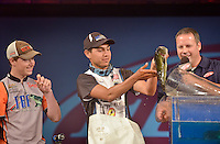 NWA Democrat-Gazette/BEN GOFF -- 04/26/15 Jacob Keenom (left) and Oklahoma teammate Trevor Yates weigh-in with FLW master of ceremonies Chris Jones on the final day of the 2015 High School Fishing National Championship at the John Q. Hammons Center in Rogers on Sunday Apr. 26, 2015. The Oklahoma team placed second in the tournament to the team from North Carolina.