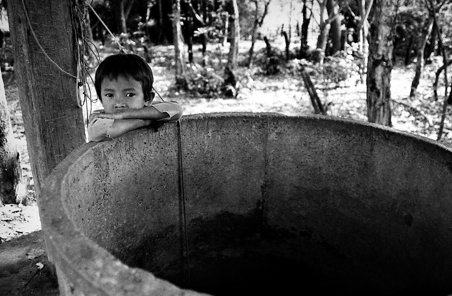 "Mekong Dam Victims - Laos. A boy leaning on to an empty well created to provide clean water to the village. After the construction of the Theun-Hinboun Dam in Laos more than 29,000 people in 71 villages have lost fisheries, rice fields, vegetables gardens and fresh drinking water supplies as a result of the dam. An expansion project is currently under construction and will displace another 4,200 mostly indigenous people from their lands in the reservoir area and displace or negatively affect another 50,000 people living downstream, on project construction lands, and in resettlement host villages. Known as ""The Mother of Waters"", more than 60 million people depend on the Mekong river and its tributaries for food, fresh water, transport and other aspects of daily life. The construction of big dams is now threatening the life of these people aswell as the vital and unique ecosystem of the river."