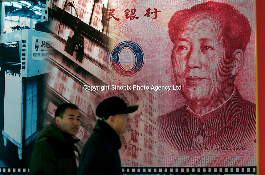 Two visitors pass by a poster showing the design and print process of Chinese currency yuan during an exhibition about finance knowledge at the National Museum of China in Beijing, China. .