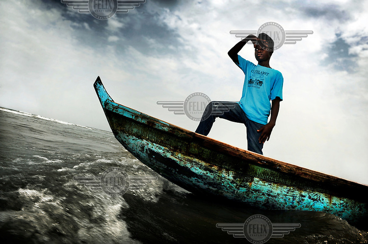 "Varney Parkir is 14 years old. Here he stands at the front of a boat. Parkir was born in Liberia and his mother died when he was a baby. His father couldn't provide for the family and his village doesn't have a school so he went to Monrovia, the capital, to go and live with his uncle. His father, stepmother and sister stayed behind in their village. Varney never goes to visit them. The people in the village were jealous of him so he doesn't feel welcome back home anymore. ""I dream of becoming a captain of a big ship. With the ship I want to travel to Robertsport in Grand Cape Mount County. That's where I was born."".."