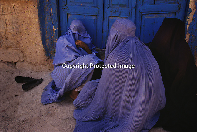 Unidentified women dressed in burqa sit outside a door on June 20, 1996 in Herat, Afghanistan. The Taliban took over most of Afghanistan in late 1996, and have forced people to live under strict Muslim sharia law. Girls were not allowed to attend schools and women not allowed to work. (Photo by: Per-Anders Pettersson)