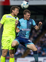 Tom Eastman of Colchester United heads clear from Dayle Southwell of Wycombe Wanderers during the Sky Bet League 2 match between Wycombe Wanderers and Colchester United at Adams Park, High Wycombe, England on 27 August 2016. Photo by Liam McAvoy.