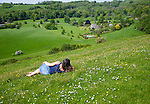 Woman lying on chalk grassland looking into deep green valley containing Rainscombe House, Oare Hill, Wiltshire, England