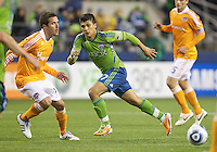 Seattle Sounders FC forward Fredy Montero makes a break after passing the ball in front of Houston Dynamo defender Hunter Freeman during play at Qwest Field in Seattle Friday March 25, 2011. The match ended in a 1-1 draw.