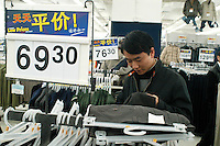 A man shops for pants, priced at less than $10 U.S. dollars, in the Beijing Wal-Mart in Beijing, China on November 6, 2005.