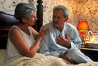 Senior man with chest pain is comforted by his concerned wife.