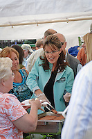Sarah Palin serves hotdogs at the Governor's Picnic in Fairbanks on her last day as Governor of Alaska.