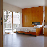 In this bedroom the door in a glass wall opens onto a large balcony and the bed is constructed of the same plywood used to line the walls