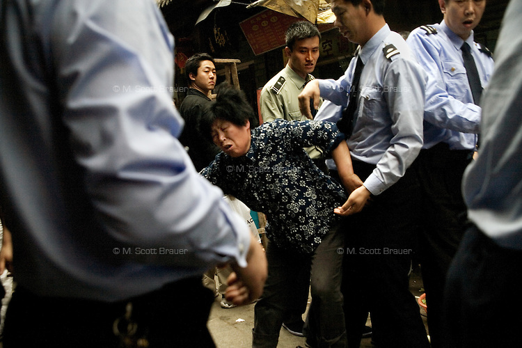 A woman fights with chengguan police as they dismantle part of her small restaurant and confiscate equipment that she stored on the sidewalk outside of her shop in the Fuzi Miao tourist market in central Nanjing, Jiangsu, China.  The chengguan, or City Urban Administrative and Law Enforcement Bureau, in Nanjing began a crackdown on sidewalk vendors and shopowners in advance of the May 1st worker's holiday.  The role of these officers lies somewhere between police and government administration, enforcing urban management policies including laws and bylaws governing sanitation, pollution, city appearance, work safety, and other issues.