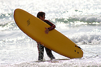 Josh , young boy carrying a foam surfboard in the surf  at Godrevy , Cornwall , July 2011 pic copyright Steve Behr / Stockfile