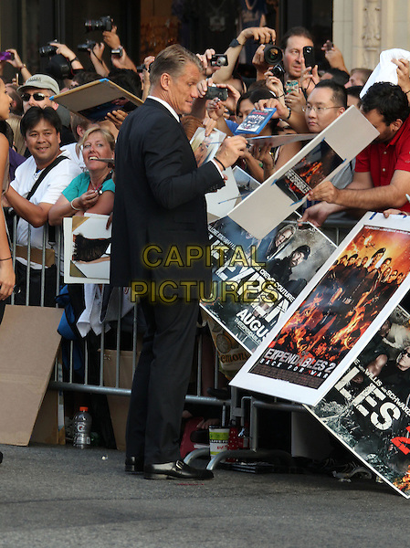 Dolph Lundgren.'The Expendables 2' premiere held at The Grauman's Chinese Theatre, Hollywood, California, USA..15th August 2012.full length black suit side profile fans crowd signing autographs .CAP/ADM/RE.©Russ Elliot/AdMedia/Capital Pictures.