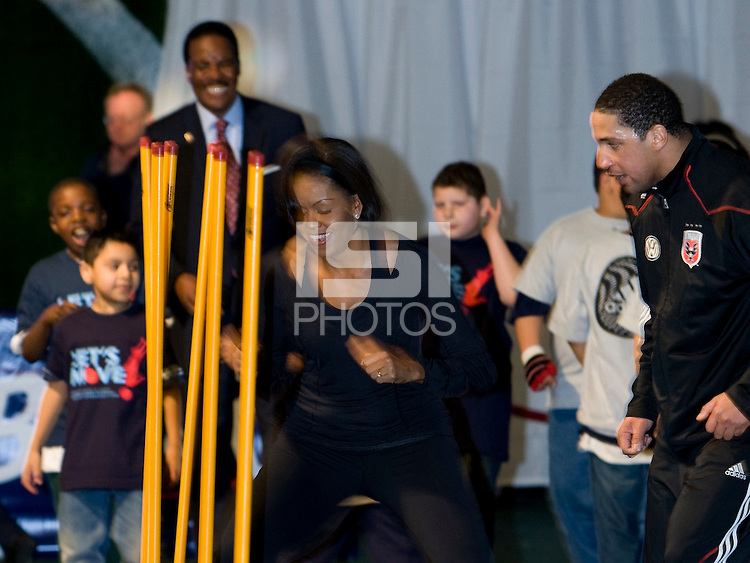First Lady Michelle Obama runs a speed drill with the encouragement of DC United's Judah Cooks during a US Soccer Foundation clinic held at City Center in Washington, DC.