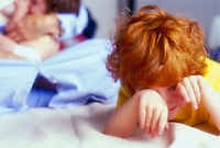 A young red-headed boy plays while his mother nurses a baby in the background.
