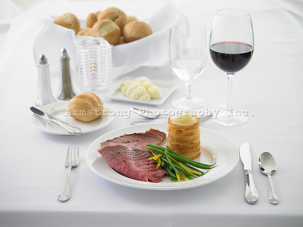 Dinner plate with roast beef, green beans, potato blinis (pancakes), dinner roll, wine. Basket of dinner rolls in background.