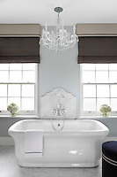 A pale blue ensuite bathroom, richly furnished with marble flooring and a free standing bath, its taps mounted on a scalloped slab of marble