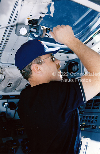 On Discovery's aft flight deck, astronaut Kenneth D. Bowersox, the STS-82 mission commander, watches as two crew members perform<br /> servicing chores on the temporarily captured Hubble Space Telescope (HST). Bowersox had earlier served on the 1993 mission (STS-61) to perform the first HST servicing chores.<br /> Credit: NASA via CNP
