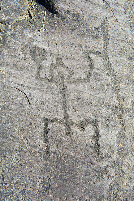 "Petroglyph, rock carving, of a schematic human figure in a ""prayer"" position wearing a crested helmet. Carved by the ancient Camuni people in the iron age between 1000-1200 BC.  Rock 21, Foppi di Nadro, Riserva Naturale Incisioni Rupestri di Ceto, Cimbergo e Paspardo, Capo di Ponti, Valcamonica (Val Camonica), Lombardy plain, Italy"