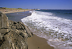Sand beach at Reid State Park, Maine, USA, showing a rocky outcrop jutting into the cold water of the Atlantic Ocean.