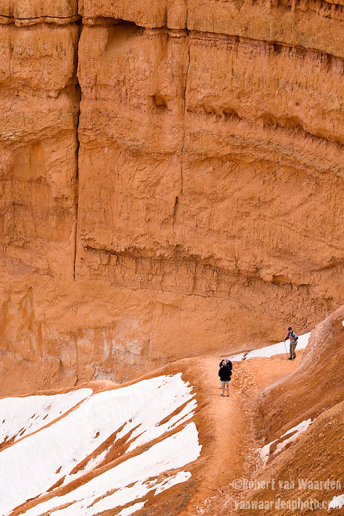 Hikers climb up the snow covered path surrounded by red hoodoos and cliffs of Bryce Canyon National Park, Utah, United States of America.