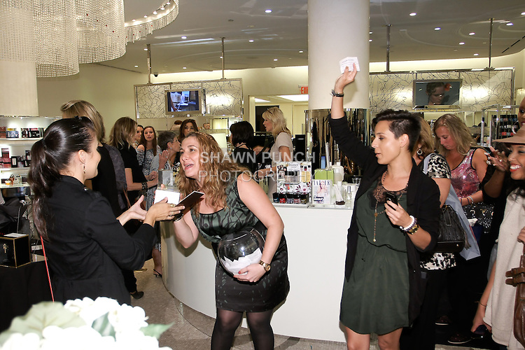 Woman wins Azagury perfume during raffle at The Plaza Hotel's Fashion's Night Out event during New York Fashion Week, September 8, 2011.