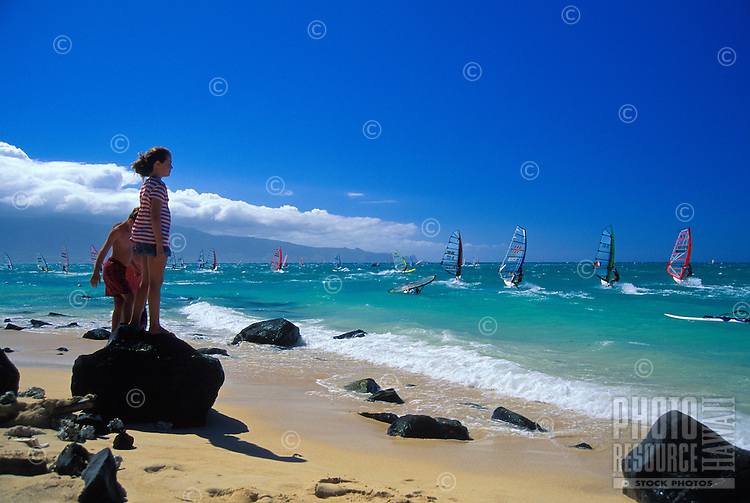 Children enjoy watching the windsurfers at Kanaha Beach Park. This is a popular beach park for both windsurfers and kitesurfers on Maui's North Shore.
