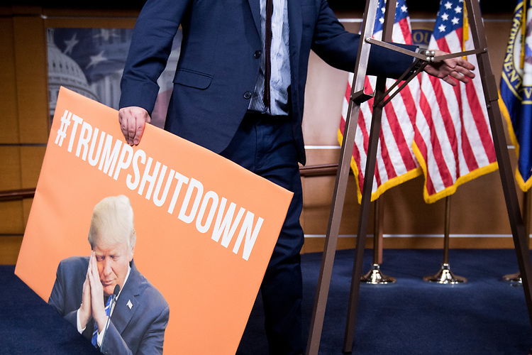 "UNITED STATES - JANUARY 21: House Minority Leader Nancy Pelosi's staff sets up a ""#TRUMPSHUTDOWN"" poster before her press conference with women House Democrats in the Capitol as the government shutdown continues on Sunday, Jan. 21, 2018. The poster was taken down before the press conference started. (Photo By Bill Clark/CQ Roll Call)"