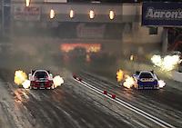Oct. 27, 2012; Las Vegas, NV, USA: NHRA funny car driver Cruz Pedregon (left) races alongside Ron Capps during qualifying for the Big O Tires Nationals at The Strip in Las Vegas. Mandatory Credit: Mark J. Rebilas-