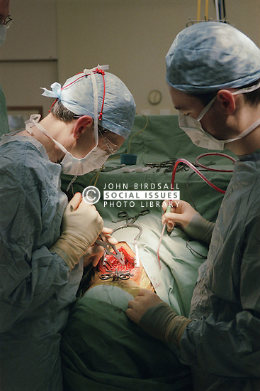 Surgeon operating on patient in hospital theatre,