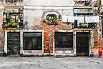 The old rustic facade of a house in the back alleys in Venice, Italy