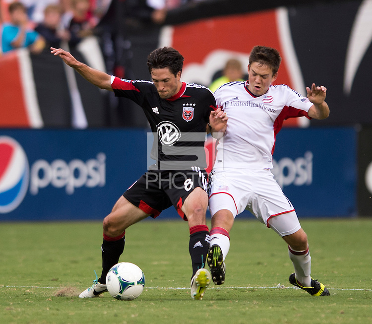 Kelyn Rowe (11) of the New England Revolution fights for the ball with John Thorrington (8) of D.C. United during a Major League Soccer game at RFK Stadium in Washington, DC.  New England defeated D.C. United, 2-1.