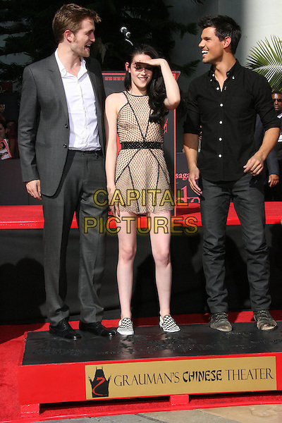 "Robert Pattinson, Kristen Stewart and Taylor Lautner .""The Twilight Trio"" Hand and Foorprint Ceremony Held at Grauman's Chinese Theatre, Hollywood, California, USA..November 2nd, 2011.full length rob suit grey gray white shirt dress beige polka dot couple black shirt jeans denim feet foot forehead profile smiling .CAP/ADM/KB.©Kevan Brooks/AdMedia/Capital Pictures."