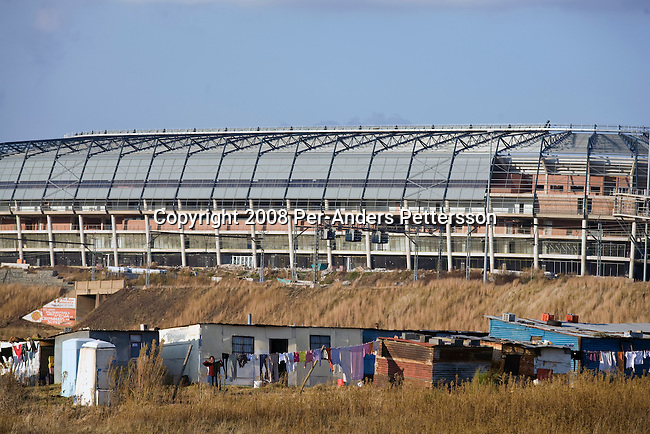 SOWETO, SOUTH AFRICA - JUNE 21:  A poor shantytown is seen in front of the newly constructed Orlando Stadium on June 21, 2008 in Soweto, South Africa. Many people still live in poverty in townships around South Africa, without proper housing, sanitation and electricity. The stadium will be used as a training ground for he upcoming Soccer World Cup in June 2010 and also used for games in the local soccer league. (Photo by: Per-Anders Pettersson/Getty Images)