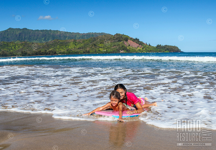 Siblings share a boogie board in Hanalei Bay, Kaua'i.