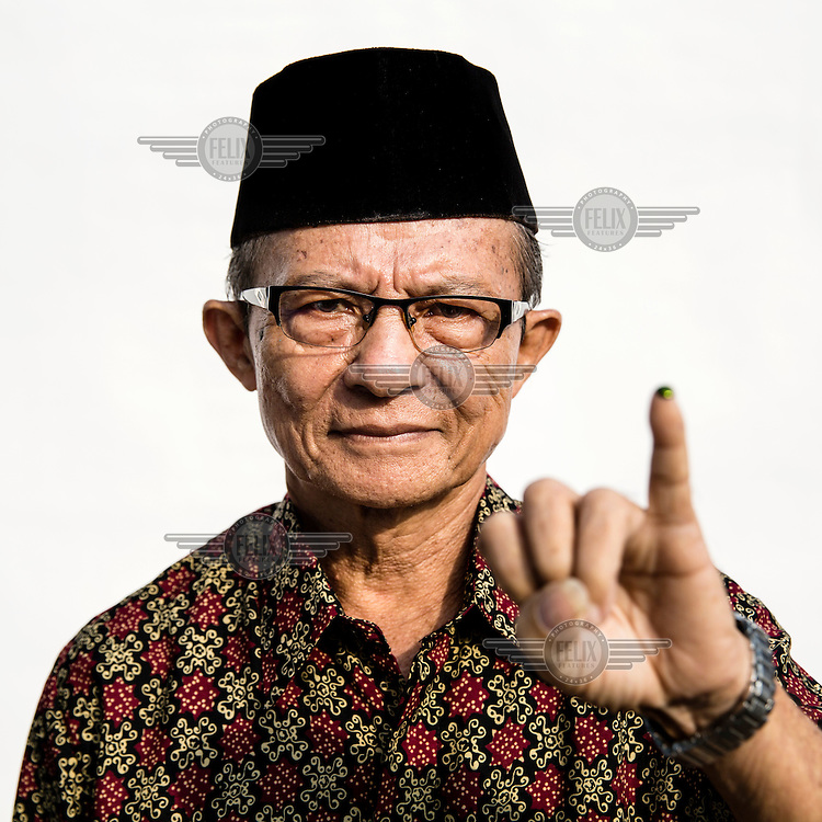 A man flashes a single finger sign, symbolising Indonesian  presidential candidate Prabowo Subianto's candidacy number after casting his vote at a polling station in Jakarta.